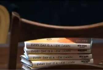 "Pile of copies of ""Every Day a New Dawn"""